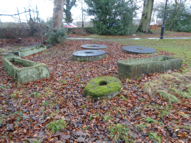 Old stone coffins or troughs and grindstones at St John the Baptist Church, Adel, Leeds. Jan 01 2017..jpg